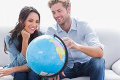 Couple looking at a globe - stock photo