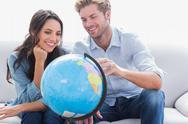 Stock Photo of Couple looking at a globe