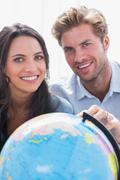 Portrait of a beautiful couple looking at a globe - stock photo