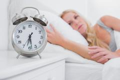 Tired woman looking at the alarm clock - stock photo