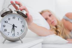 Tired woman turning off the alarm clock - stock photo