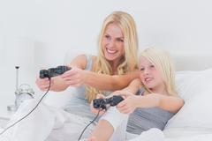 Cheerful mother and daughter playing video games Stock Photos