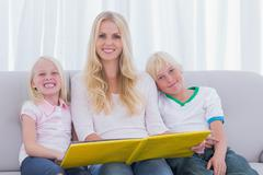 Portrait of a mother reading a story to children - stock photo