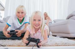 Siblings playing video games - stock photo