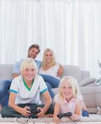 Children on the carpet playing video games - stock photo