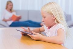 Little girl using tablet while her mother is reading on the couch Stock Photos