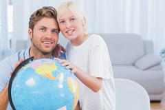 Stock Photo of Father and his son looking at globe and smiling