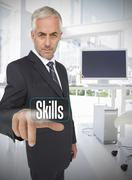 Stock Photo of Businessman selecting the word skills