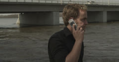 4K Ultra High Definition - Man on Cell Phone in Front of Bridge Stock Footage