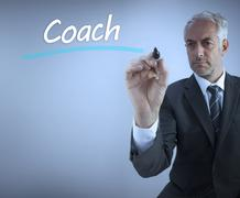 Businessman writing the word coach - stock photo