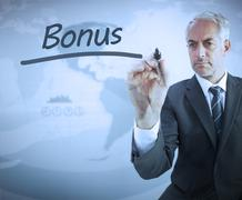 Businessman writing the word bonus - stock photo