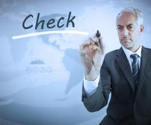 Stock Photo of Businessman writing the word check