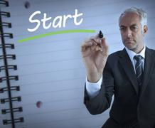 Businessman standing and writing the word start - stock photo