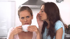 Woman whispering gossips to a friend holding a cup of coffee Stock Footage