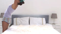 Cute woman falling on her bed full of pillow feathers Stock Footage