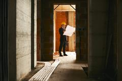 architect standing in house under construction with building plan - stock photo