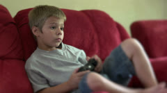 Child playing video game sitting on couch Stock Footage