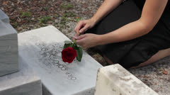 Female holding a rose while kneeling at a grave close Stock Footage