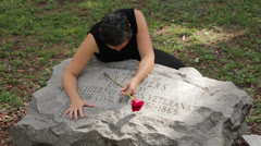Grieving woman laying over a grave Stock Footage
