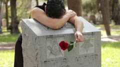 Grieving woman with her head on her parent's grave 2 Stock Footage