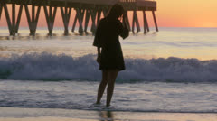 Pensive woman walks on beach, pier, birds, dusk, panning, 48fps -CC -lev Stock Footage
