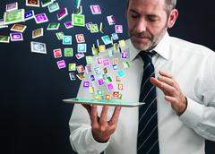 tablet pc with cloud of application icons flying arround - stock illustration