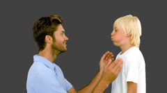 Stock Video Footage of Man pressing inflated cheeks of his son on grey background