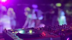 DJ hands and equipment during night club party with dancing people Stock Footage