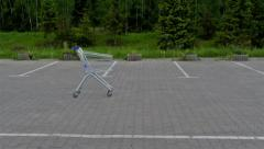 Shopping cart on empty parking lot. - stock footage