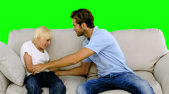 Father tickling his son on the sofa on green screen Stock Footage