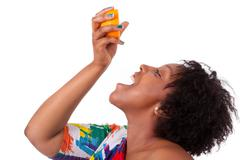 overweight young black woman drinking orange juice - african people - stock photo