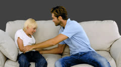 Father tickling son on the sofa on grey background Stock Footage