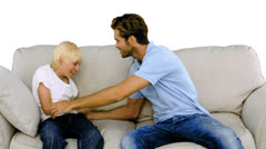 Father tickling son on the sofa on white background Stock Footage