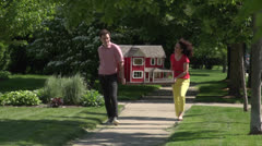 Couple carrying a dollhouse down a sidewalk Stock Footage