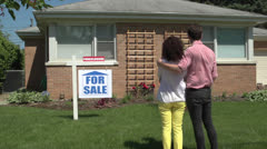 Young couple standing outside a foreclosed house, wide dolly. Stock Footage