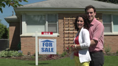Happy young couple standing outside a sold house. Stock Footage