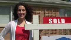 Woman standing next to a for sale sign, close up. Stock Footage