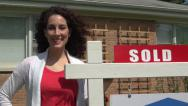 Stock Video Footage of Woman standing next to a for sale sign, close up.