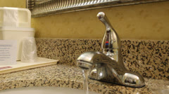 Bathroom countertop in hotel with water running from faucet Stock Footage