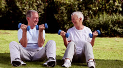 Mature couple sat on the grass lifting dumbbells - stock footage
