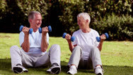Stock Video Footage of Mature couple sat on the grass lifting dumbbells