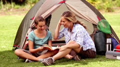 Mother and daughter reading a book in front of their tent Stock Footage