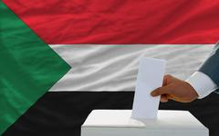 Stock Photo of man voting on elections in sudan in front of flag
