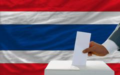 Stock Photo of man voting on elections in thailand in front of flag