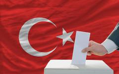 man voting on elections in turkey in front of flag - stock photo