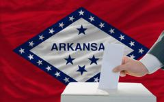 man voting on elections in front of flag us state flag of arkansas - stock photo
