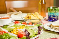Traditional mexican food with a plate of fresh salad, tortillas, chicken faji Stock Photos