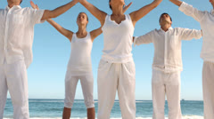Peaceful people practicing yoga the beach - stock footage