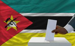 Stock Photo of man voting on elections in front of national flag of mozambique