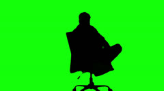 Silhouette of man turning of swivel chair on green screen Stock Footage